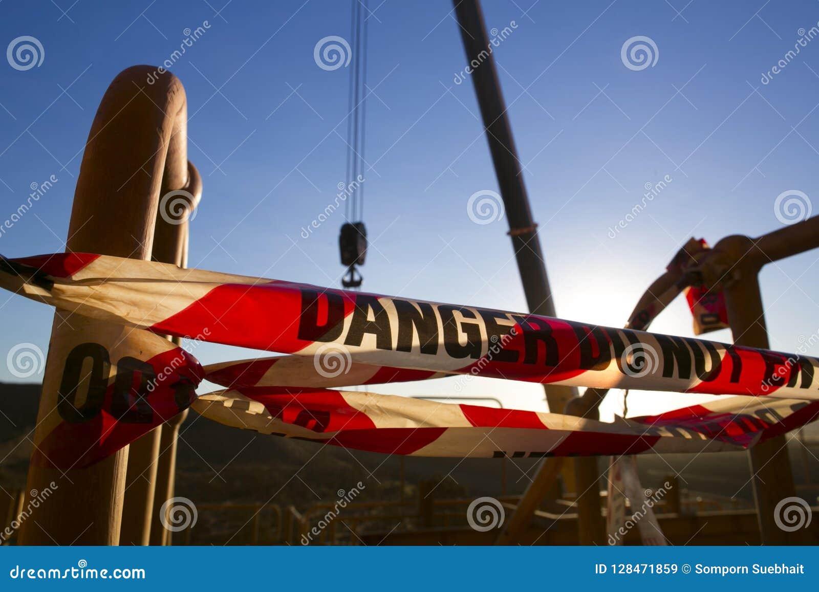 在录音操作范围的禁区的红色和白色危险标记磁带标志投下了举高危险的工作的对象起重机