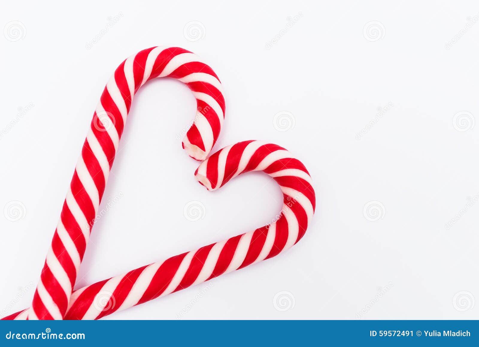 在心脏形状的红白的棒棒糖在白色背景的.图片