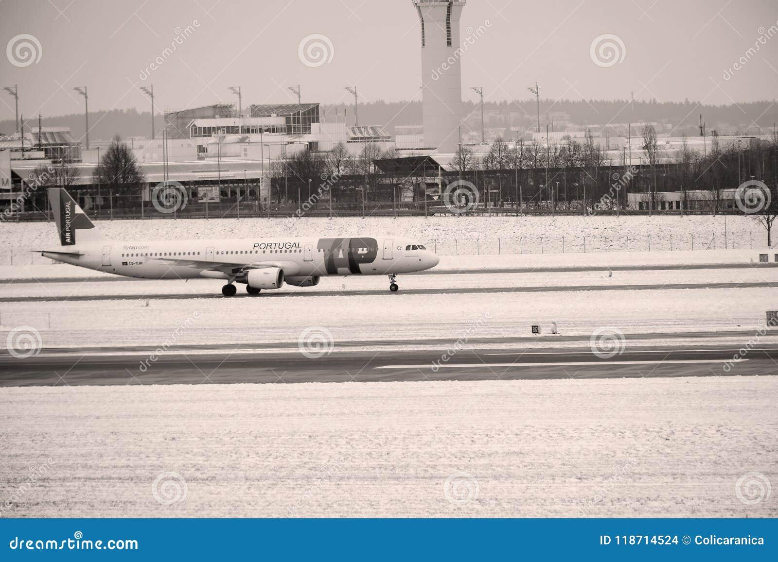 在慕尼黑机场,德国,与雪的冬时轻拍在跑道的葡萄牙航空飞机