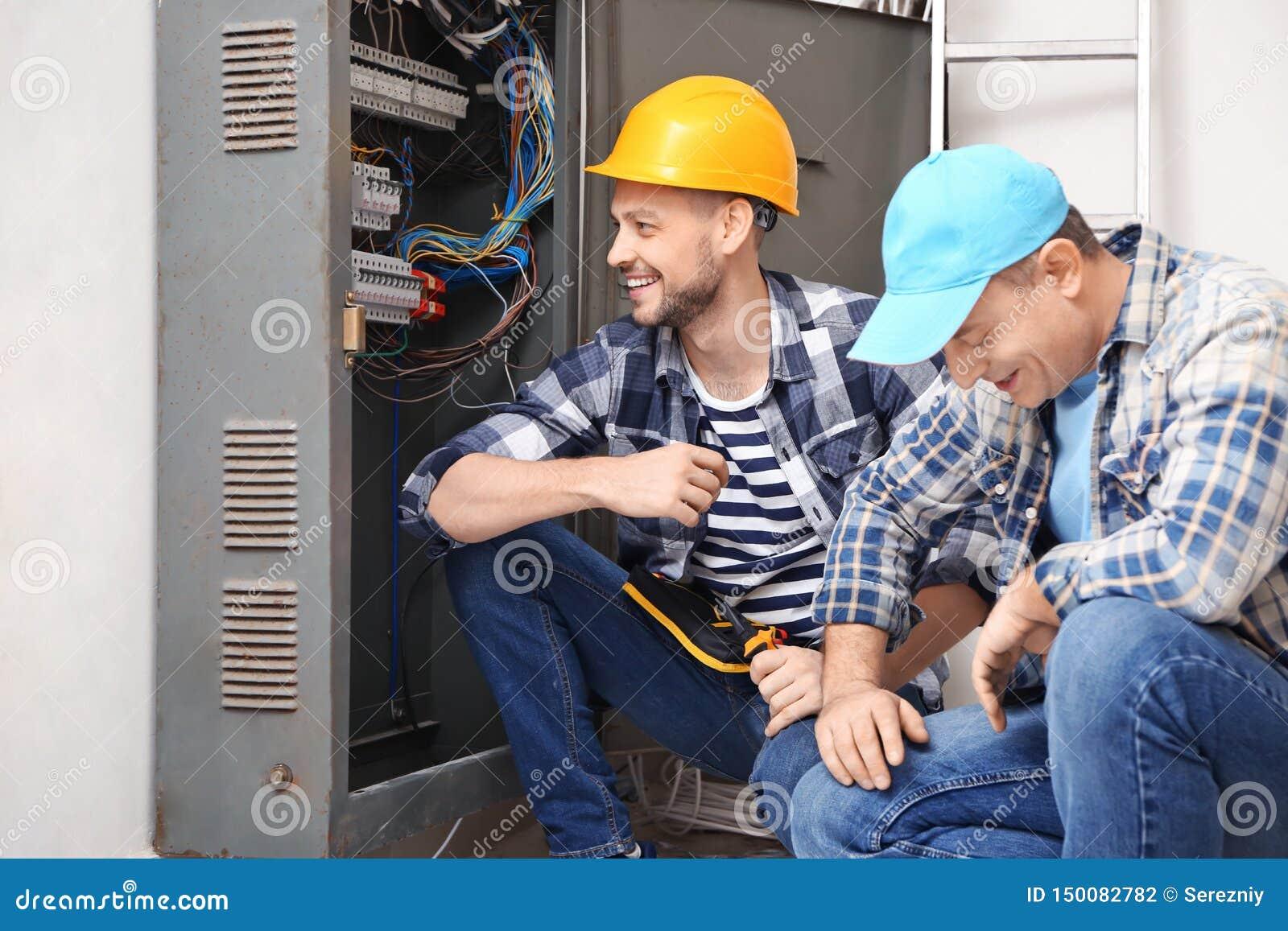 在户内配电屏附近的两位电工