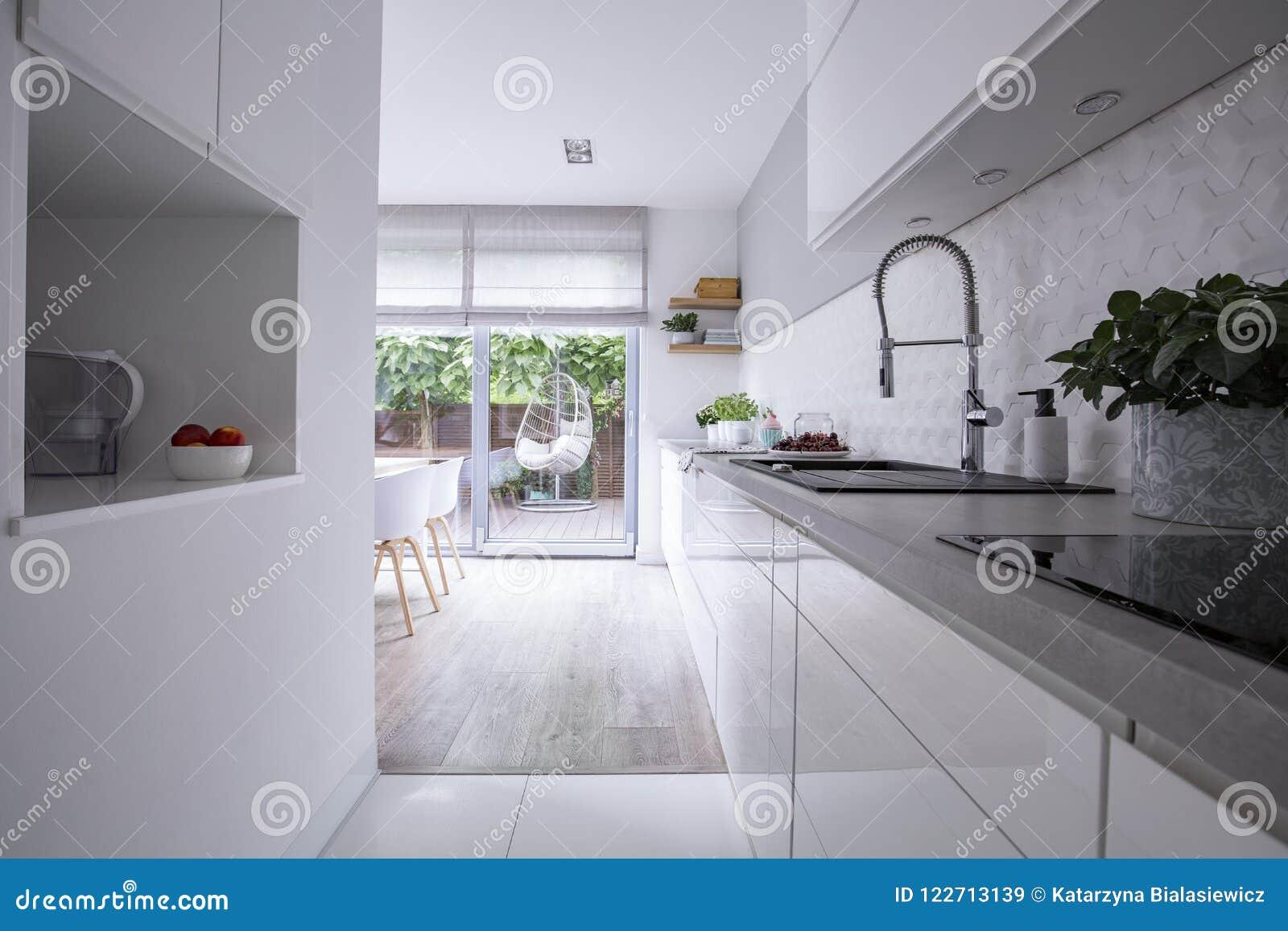 在房子明亮的现代厨房内部的白色内阁有大阳台的 实际照片