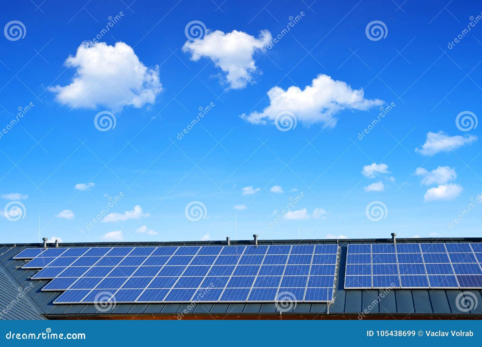 在房子的屋顶的太阳能盘区背景蓝天的