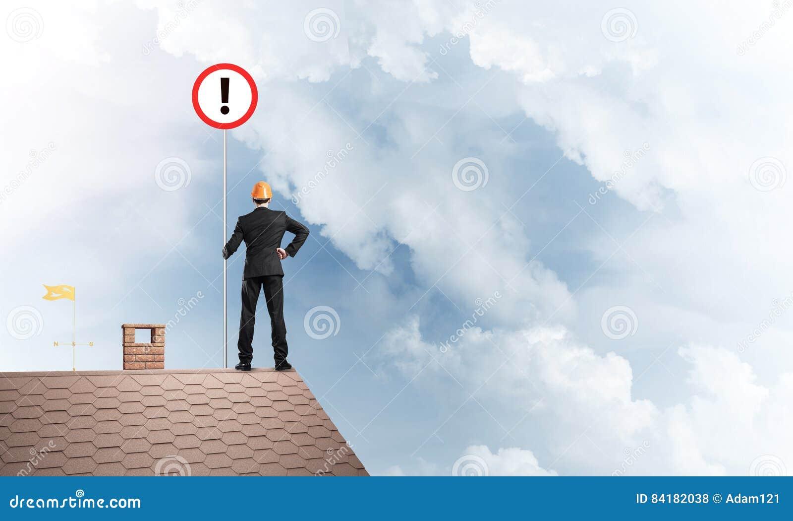 在房子顶面显示的标志的商人与惊叹号 混合