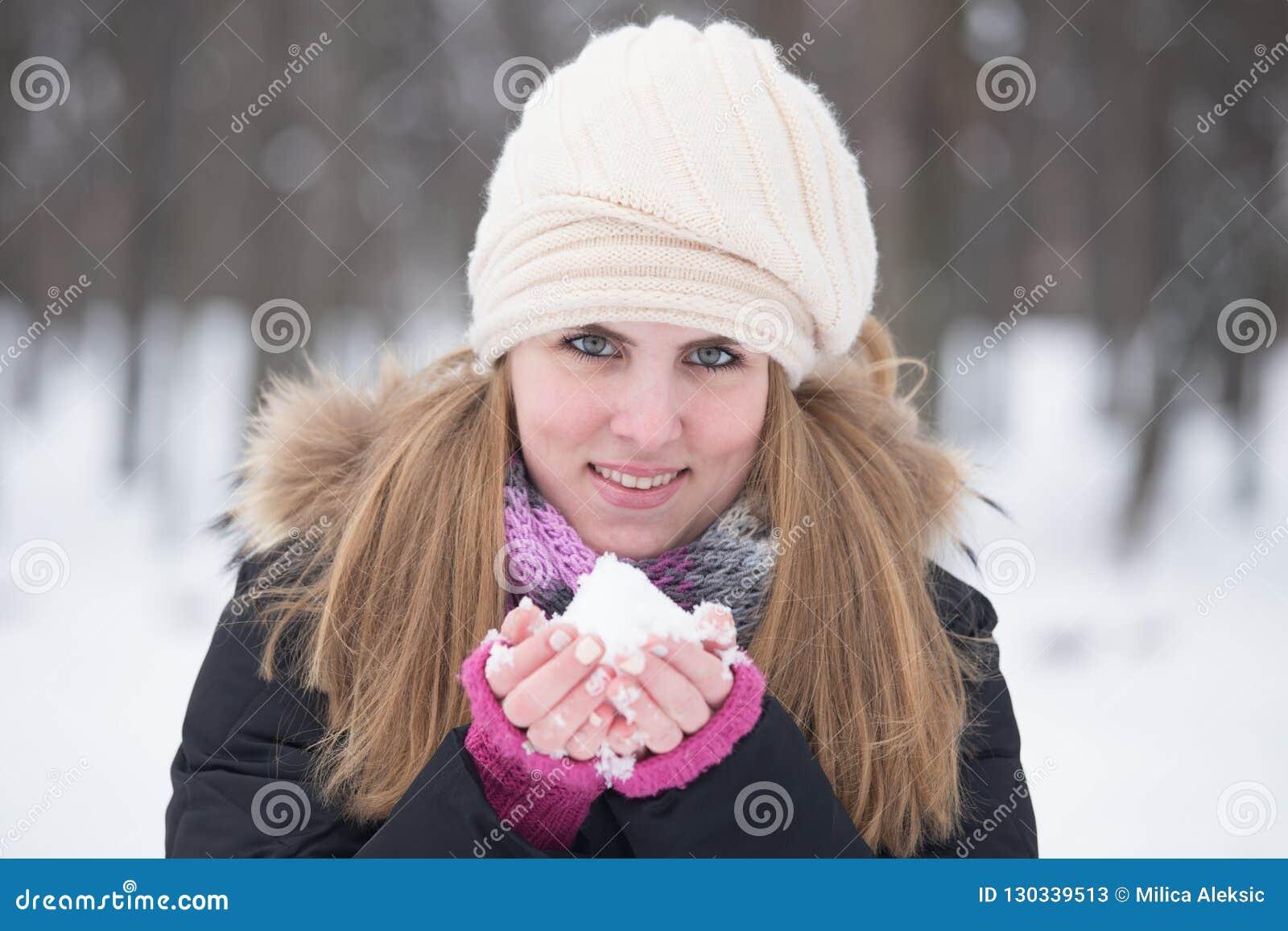 在手中拿着雪的一俏丽的少女和看照相机