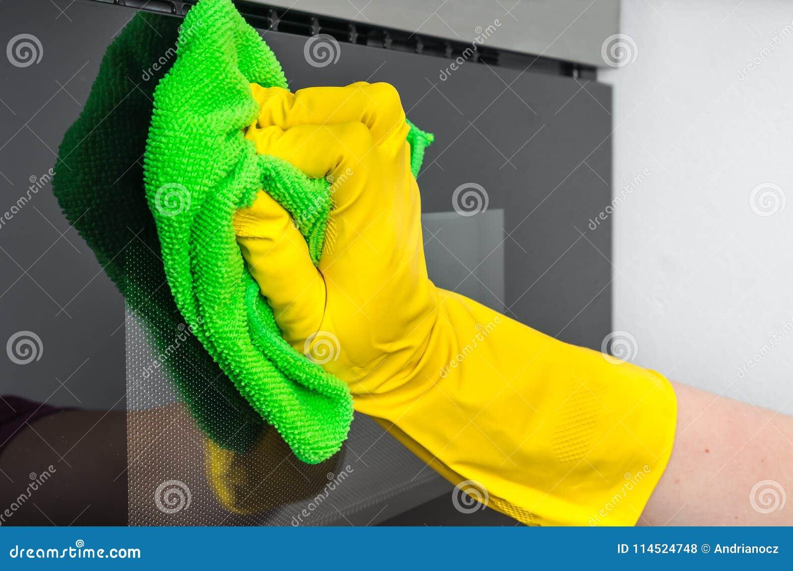 在手套的手与抹微波炉的绿色旧布