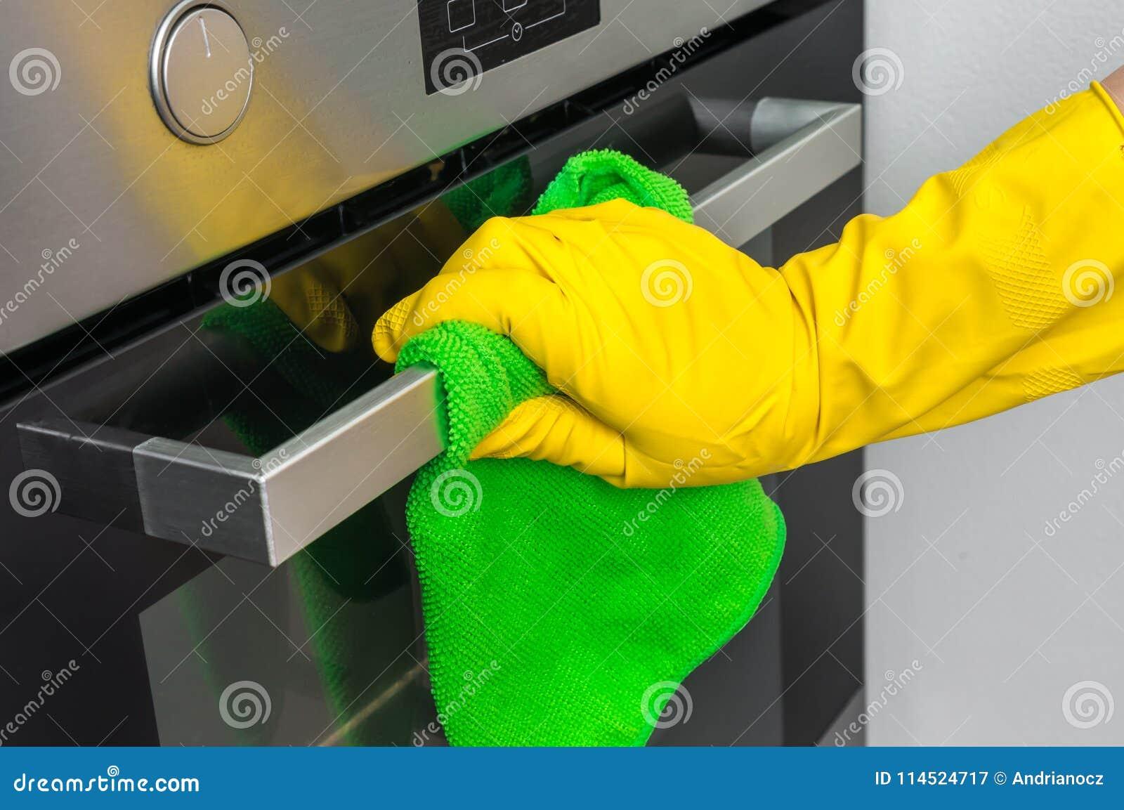 在手套的手与绿色旧布在厨房里抹烤箱