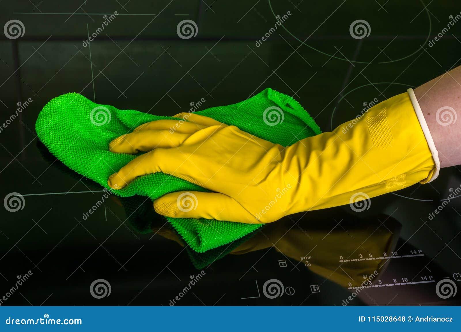在手套的手与绿色旧布抹归纳板材