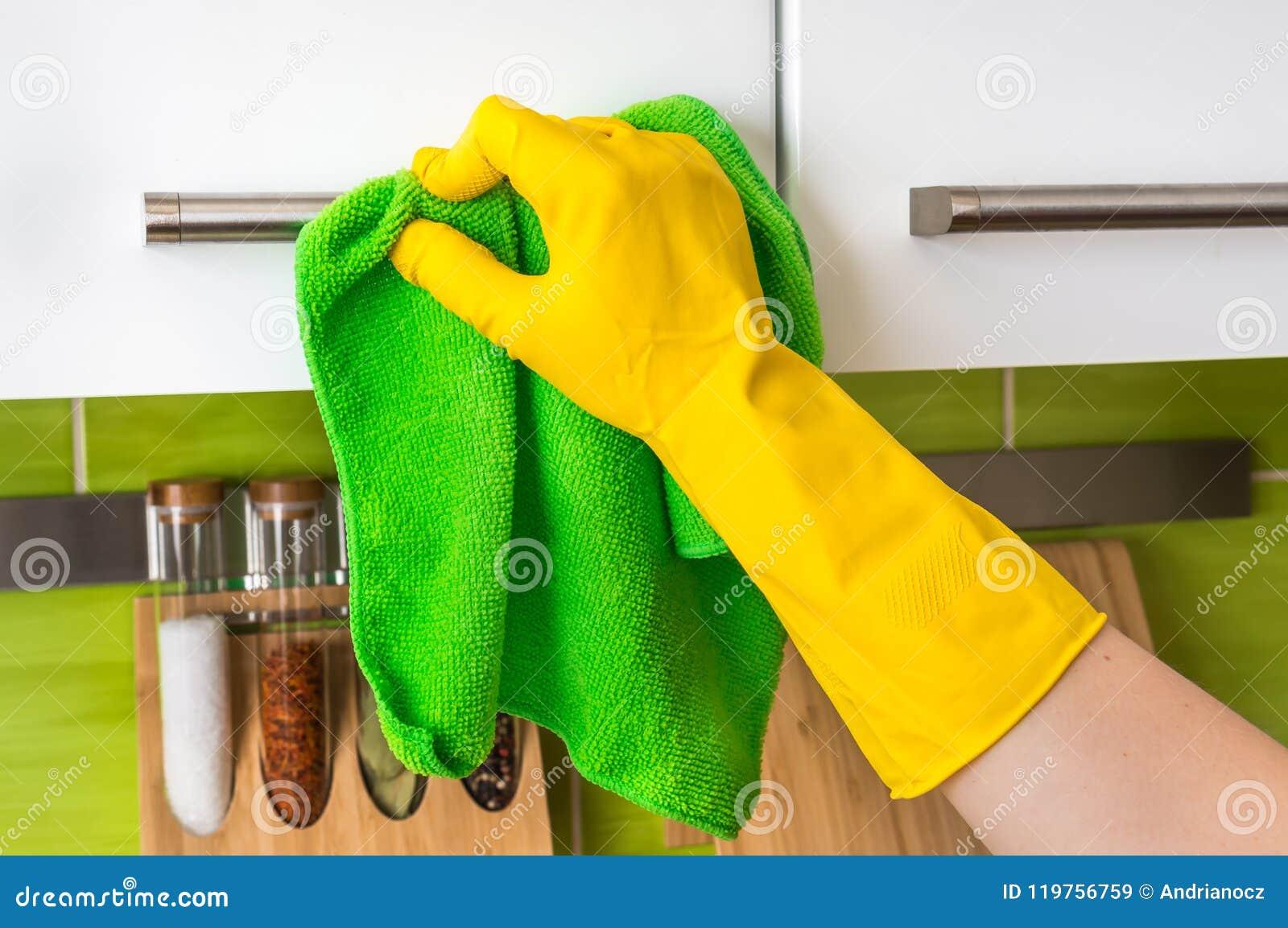 在手套的手与绿色旧布清洗不锈钢把柄