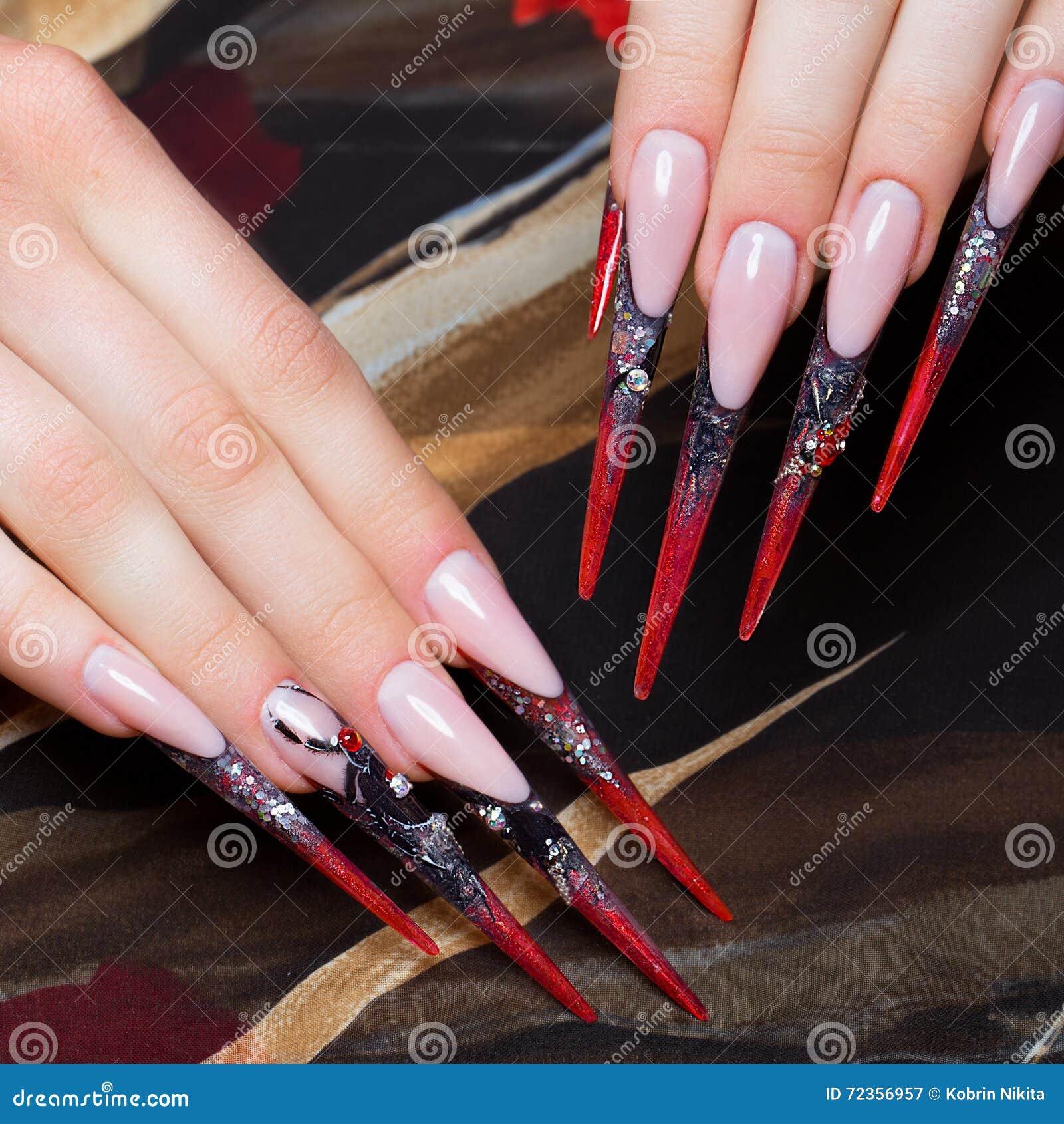 在手指的长的美好的修指甲在与蜘蛛的黑和红颜色 钉子设计 特写镜头