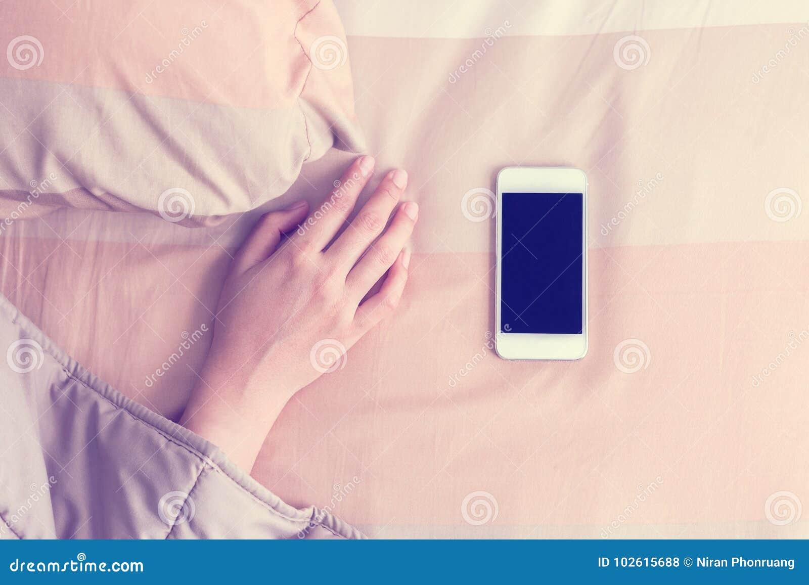 在手机醒来的毯子下的妇女手
