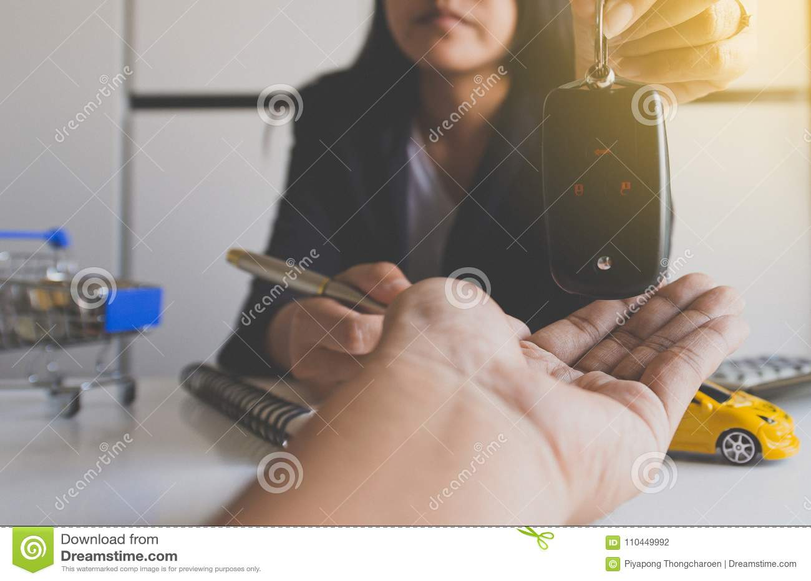 在手边给汽车钥匙车销售协定、汽车财务和贷款概念的