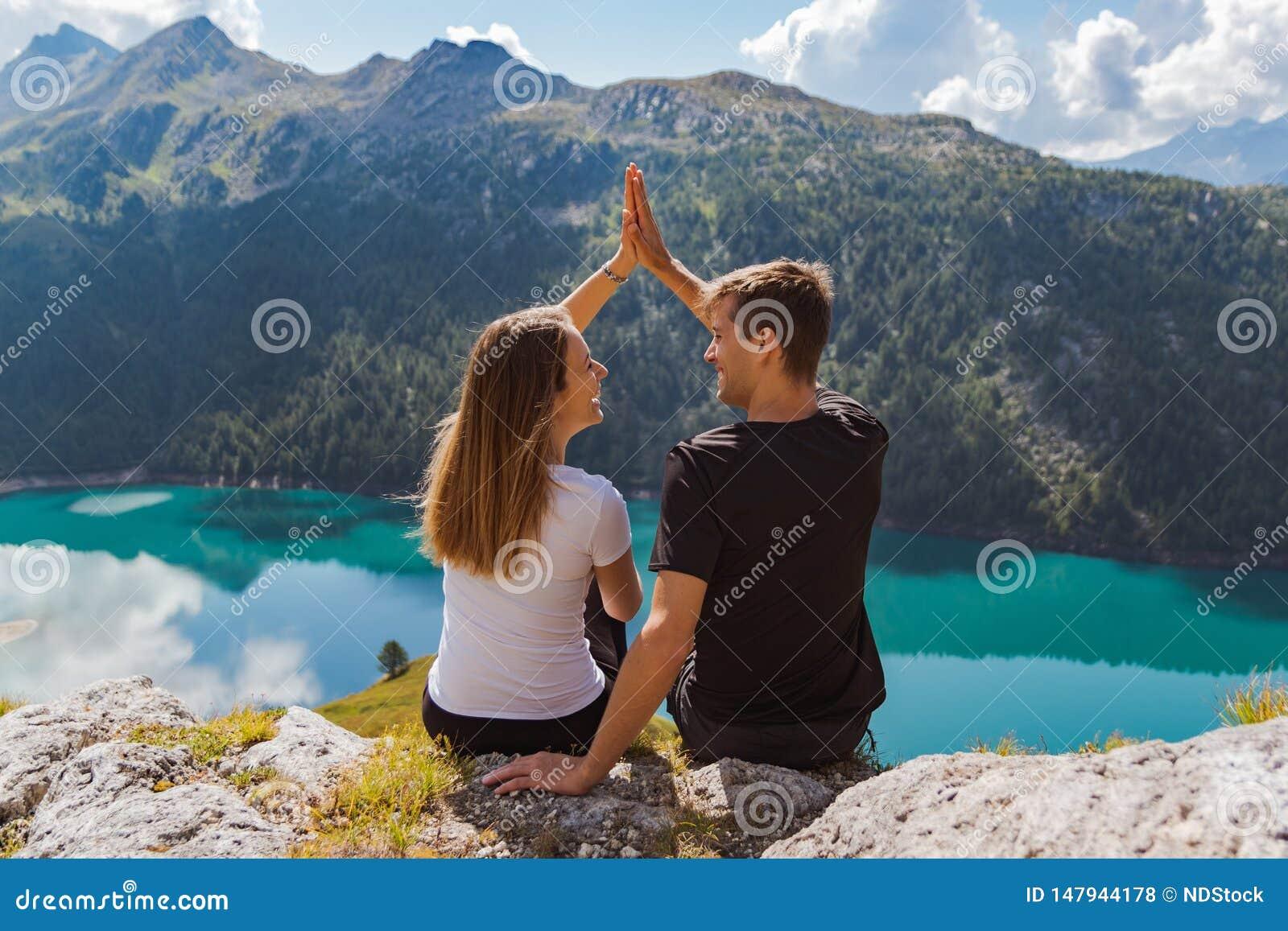 在打高五在与美好的全景的一个岩石的爱的年轻夫妇作为背景 瑞士阿尔卑斯