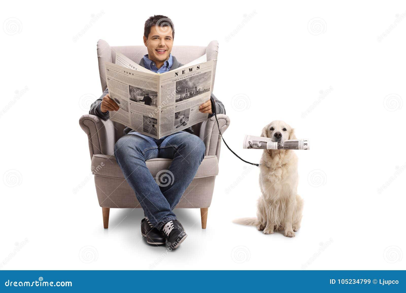 在扶手椅子安装的年轻人拿着报纸和labrad