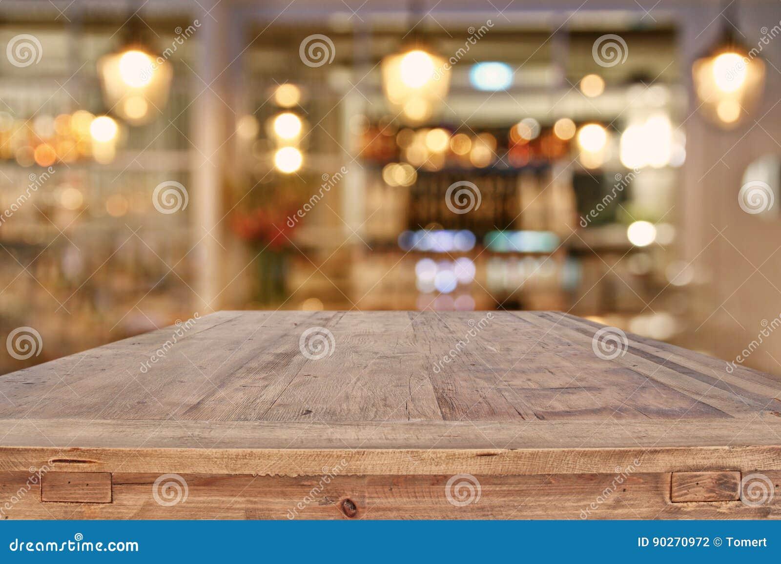 在抽象餐馆前面的木桌点燃背景