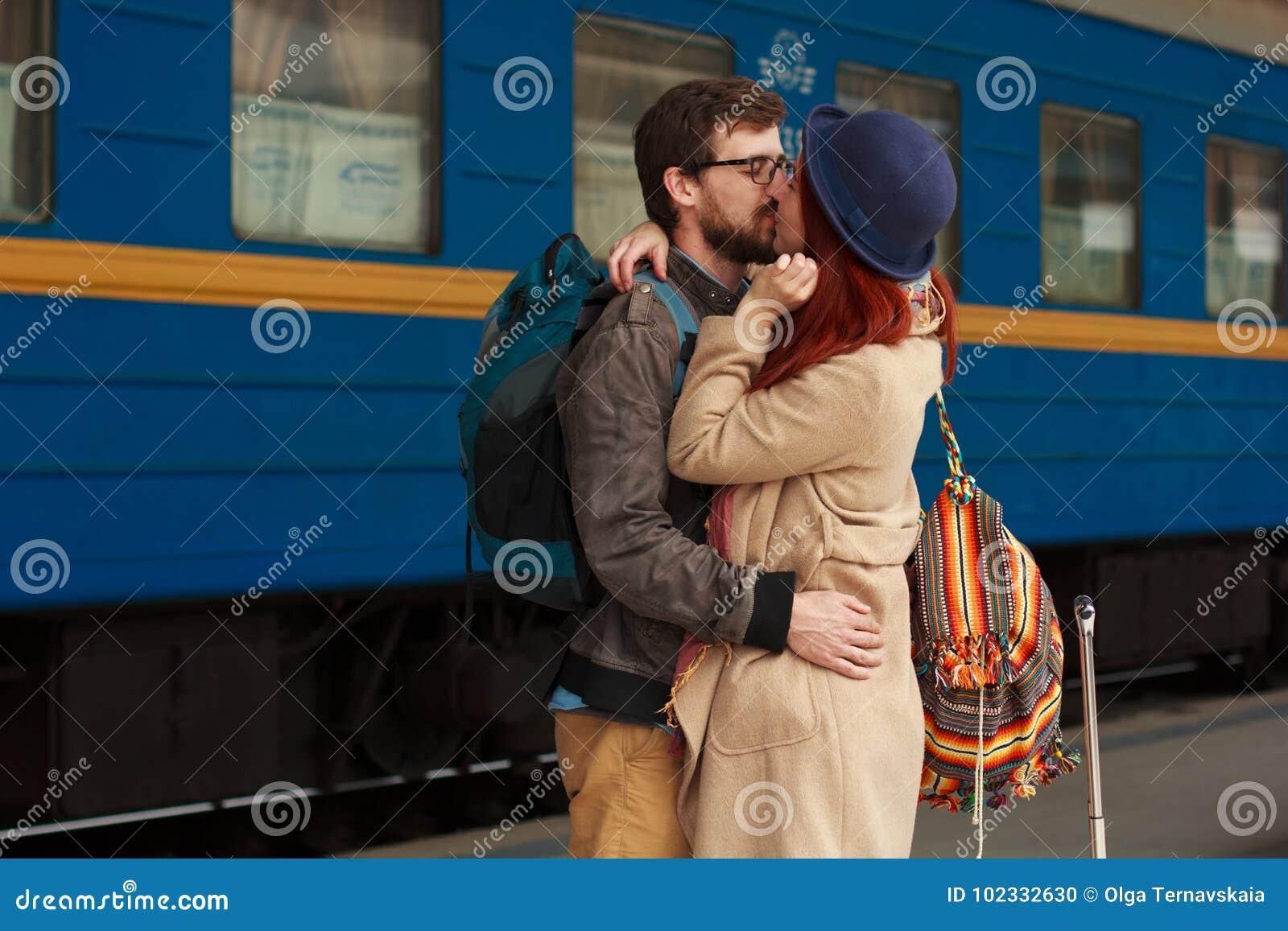 在拥抱在火车站的街道的一对愉快的夫妇的旅行的以后遭遇 美好的晚上温暖的阳光