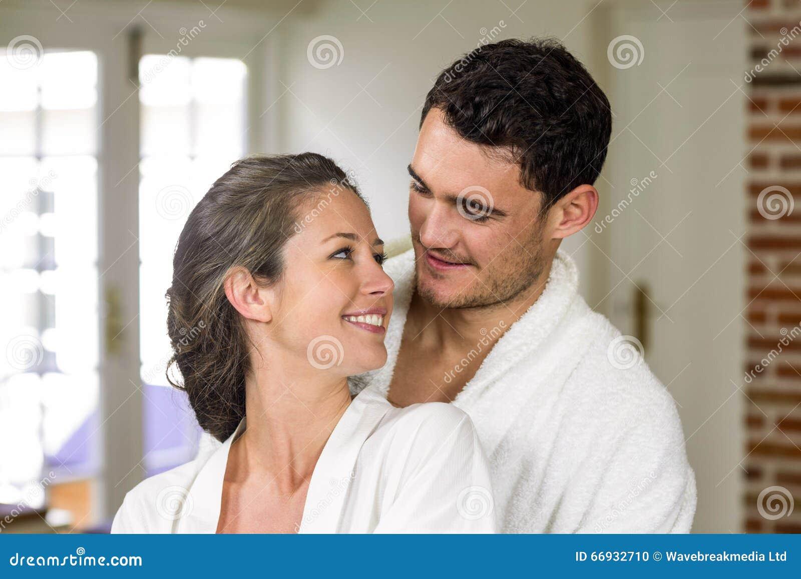 在微笑的浴巾的夫妇,当拥抱在厨房里时.图片