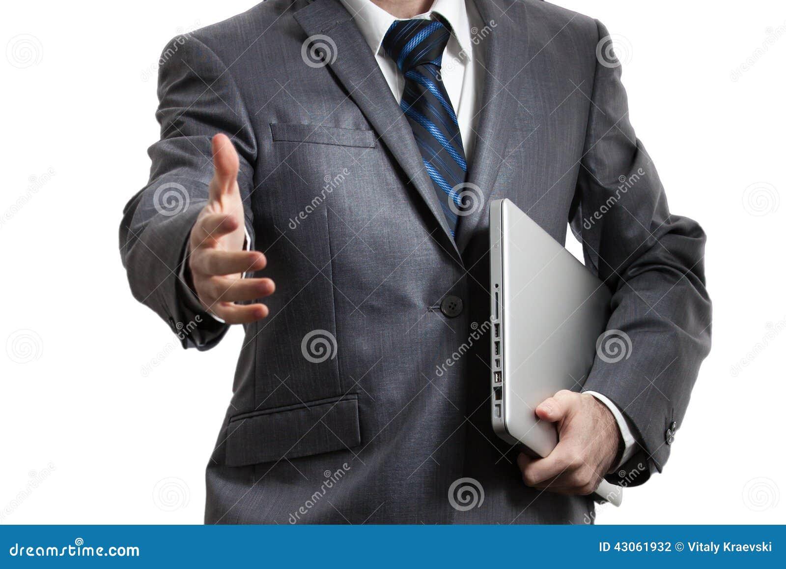 在拿着在一条胳膊的灰色衣服的商人膝上型计算机