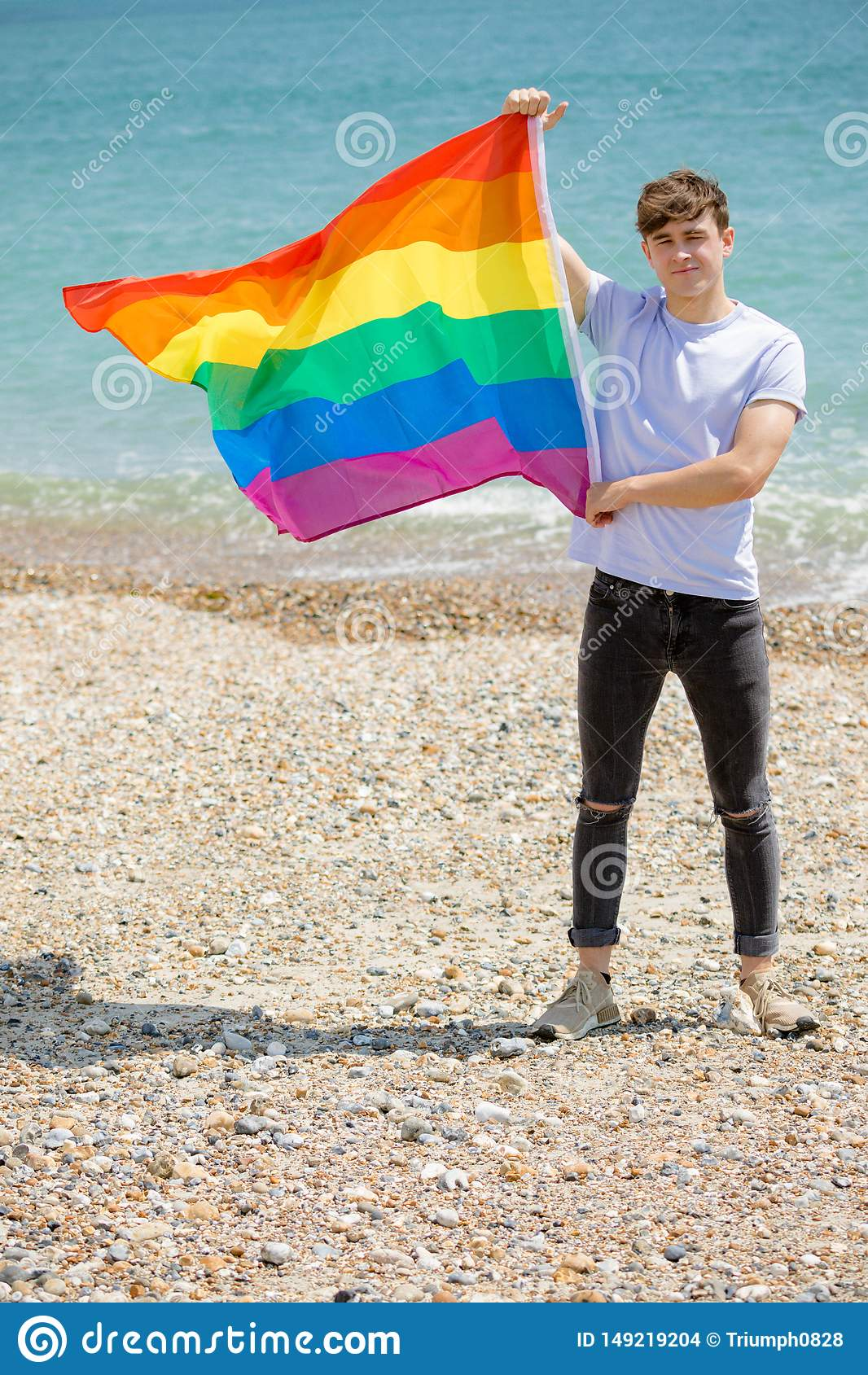 在拿着自豪感旗子的海滩的白种人男性