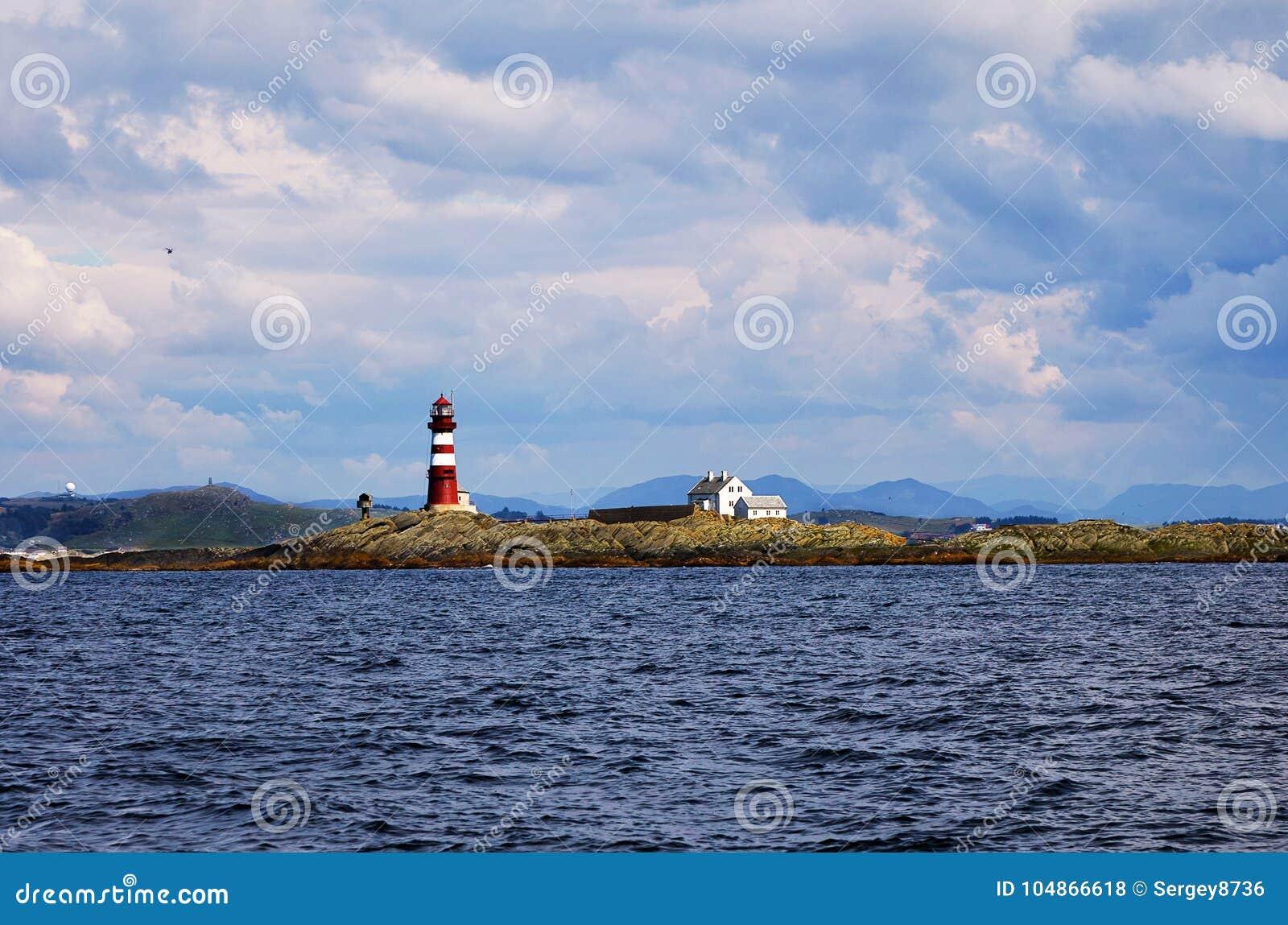 在挪威海岛上的灯塔在多云天