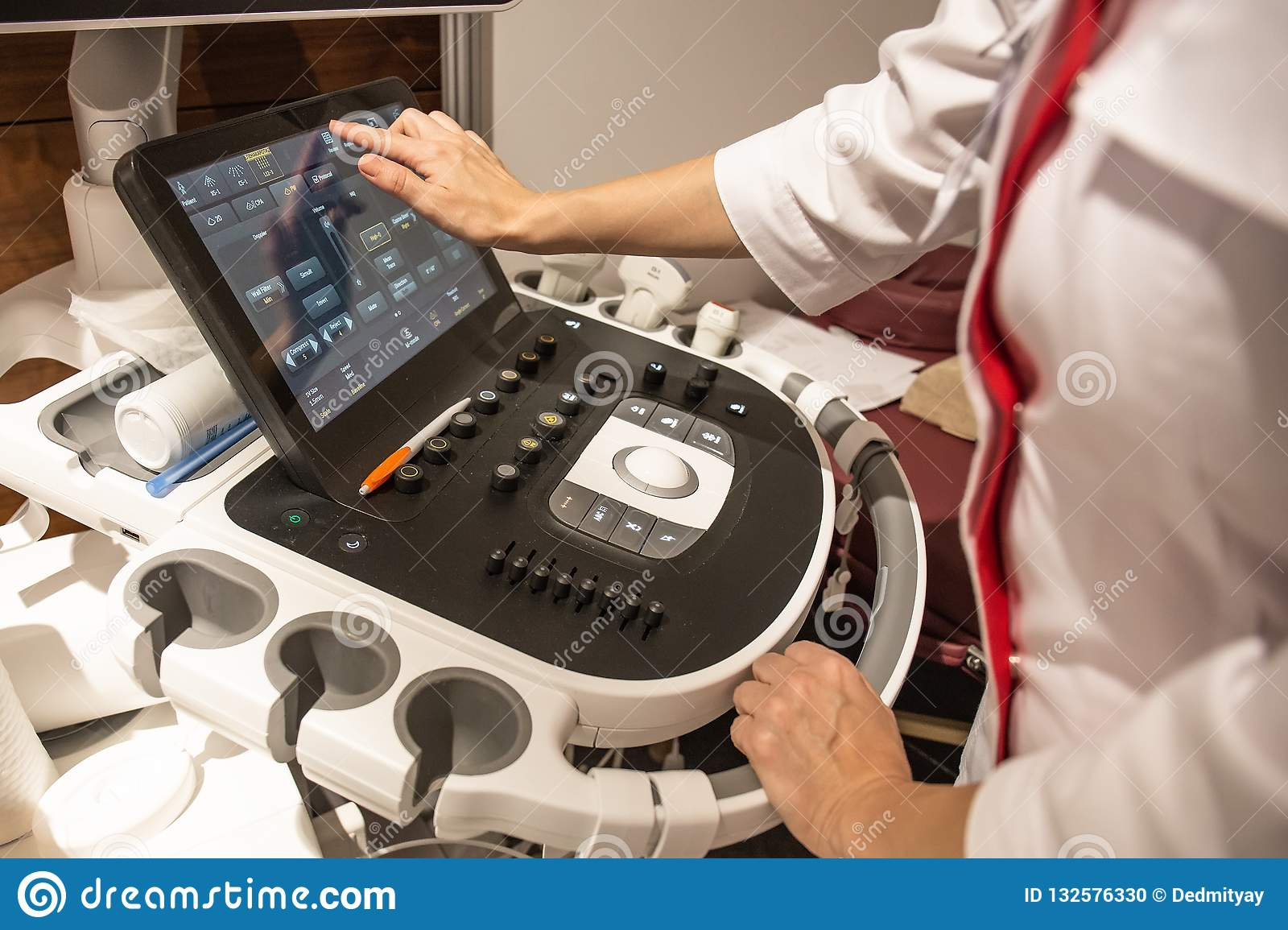 在控制板的医生手与医疗在诊所的超声波诊断设备键盘