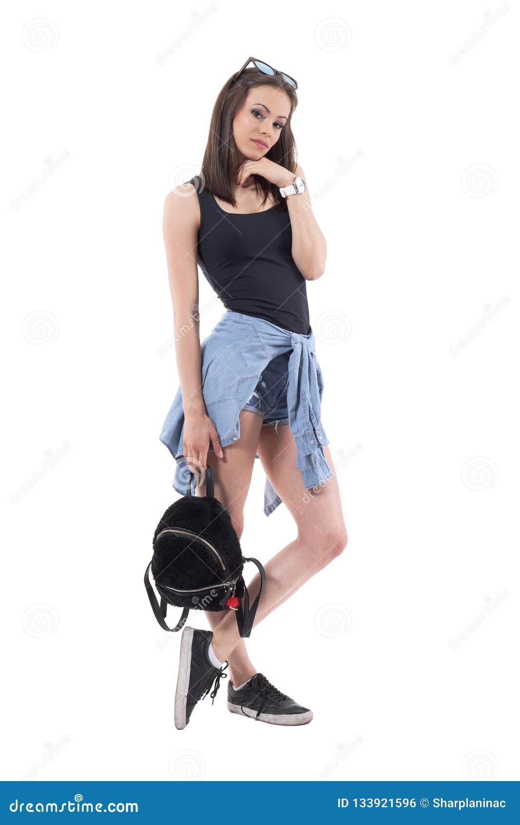 在摆在用手的街道样式现代衣裳的时髦的深色的时装模特儿在下巴藏品袋子下
