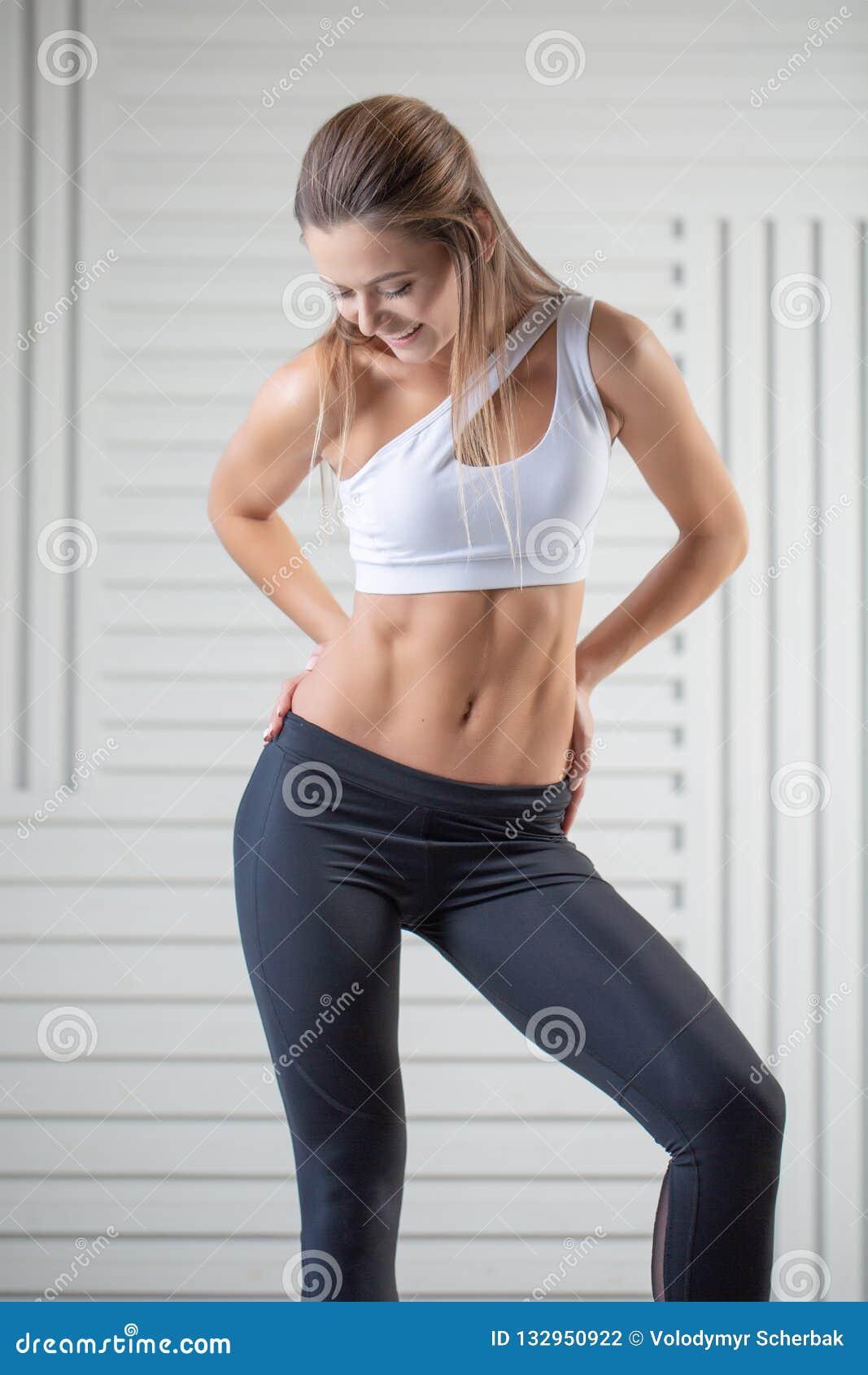 在摆在白色背景的运动服的可爱的年轻成人 有完善的身体的性感和肉欲的深色的妇女