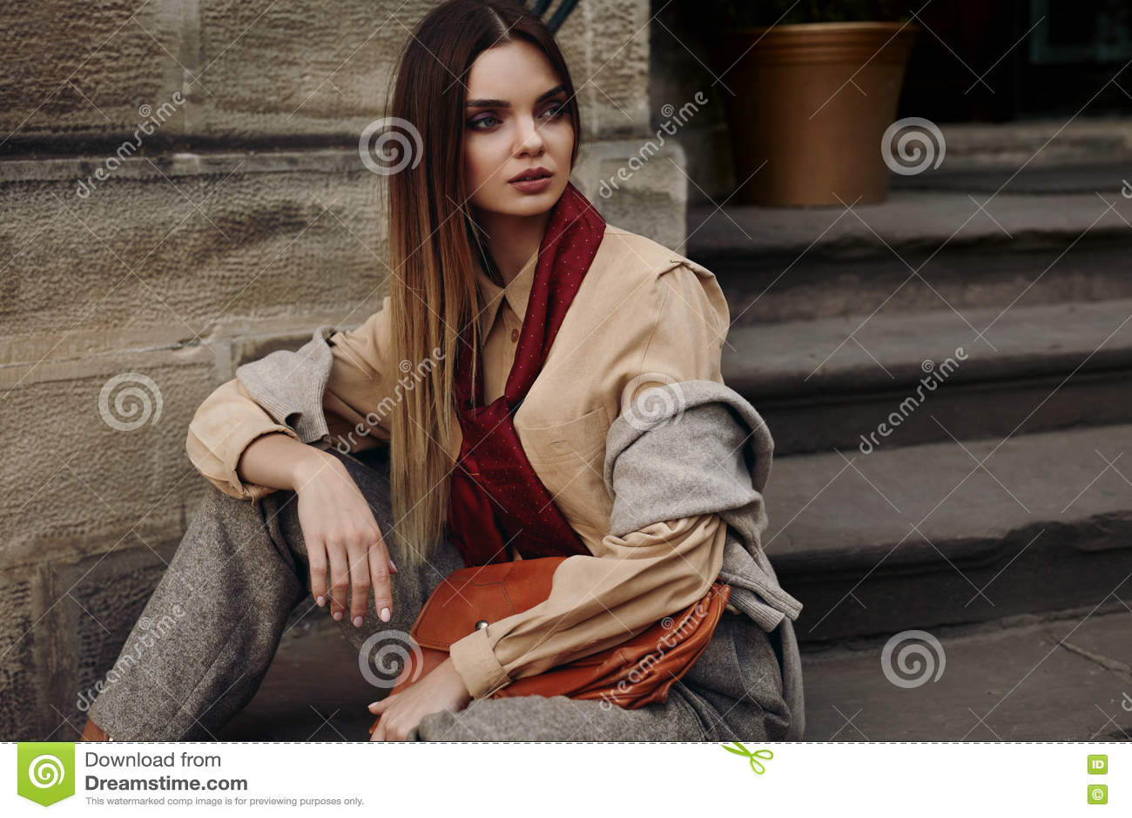 在摆在街道的流行的服装的时尚女性模型