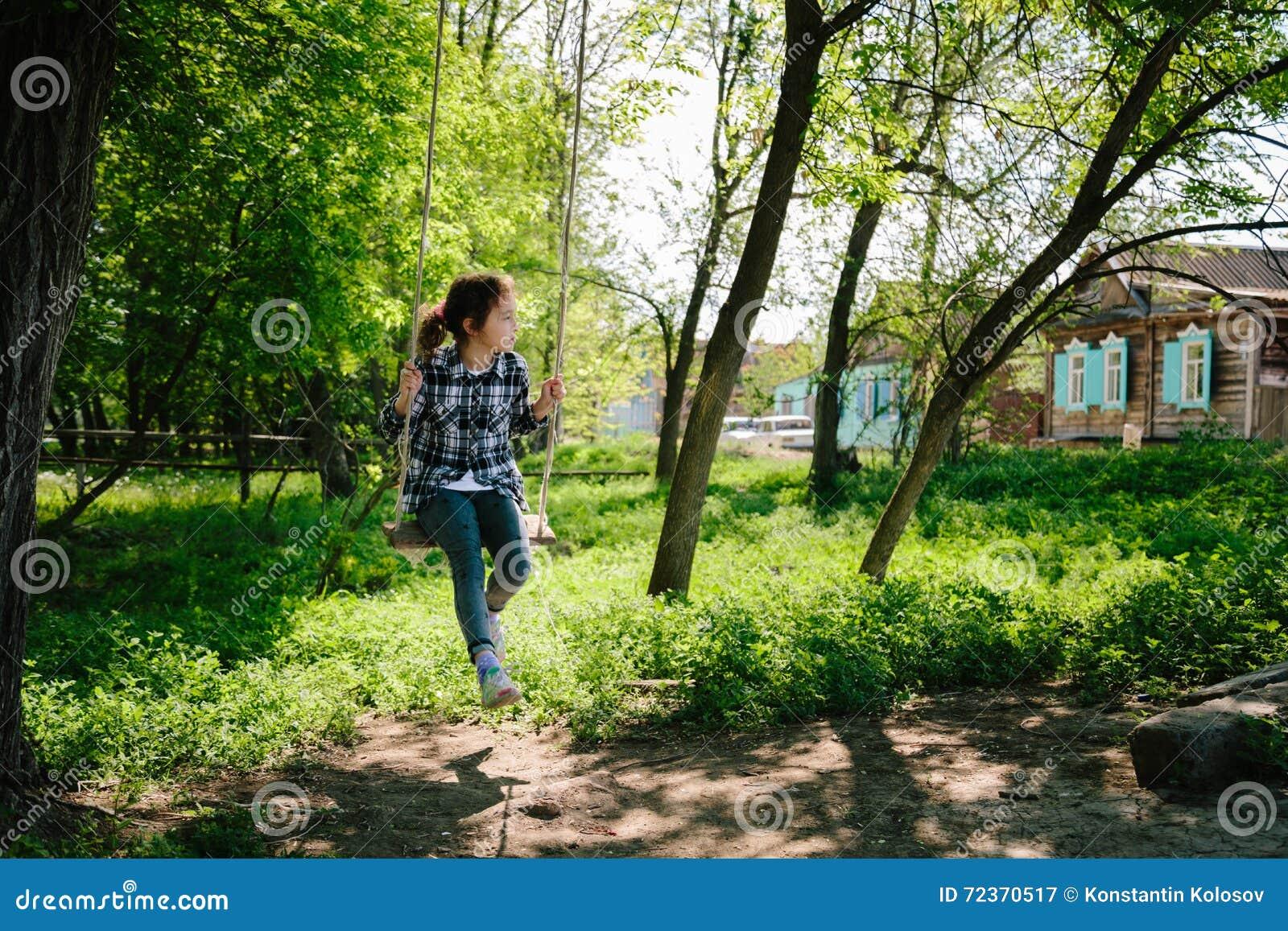 在摇摆的女孩骑马在村庄