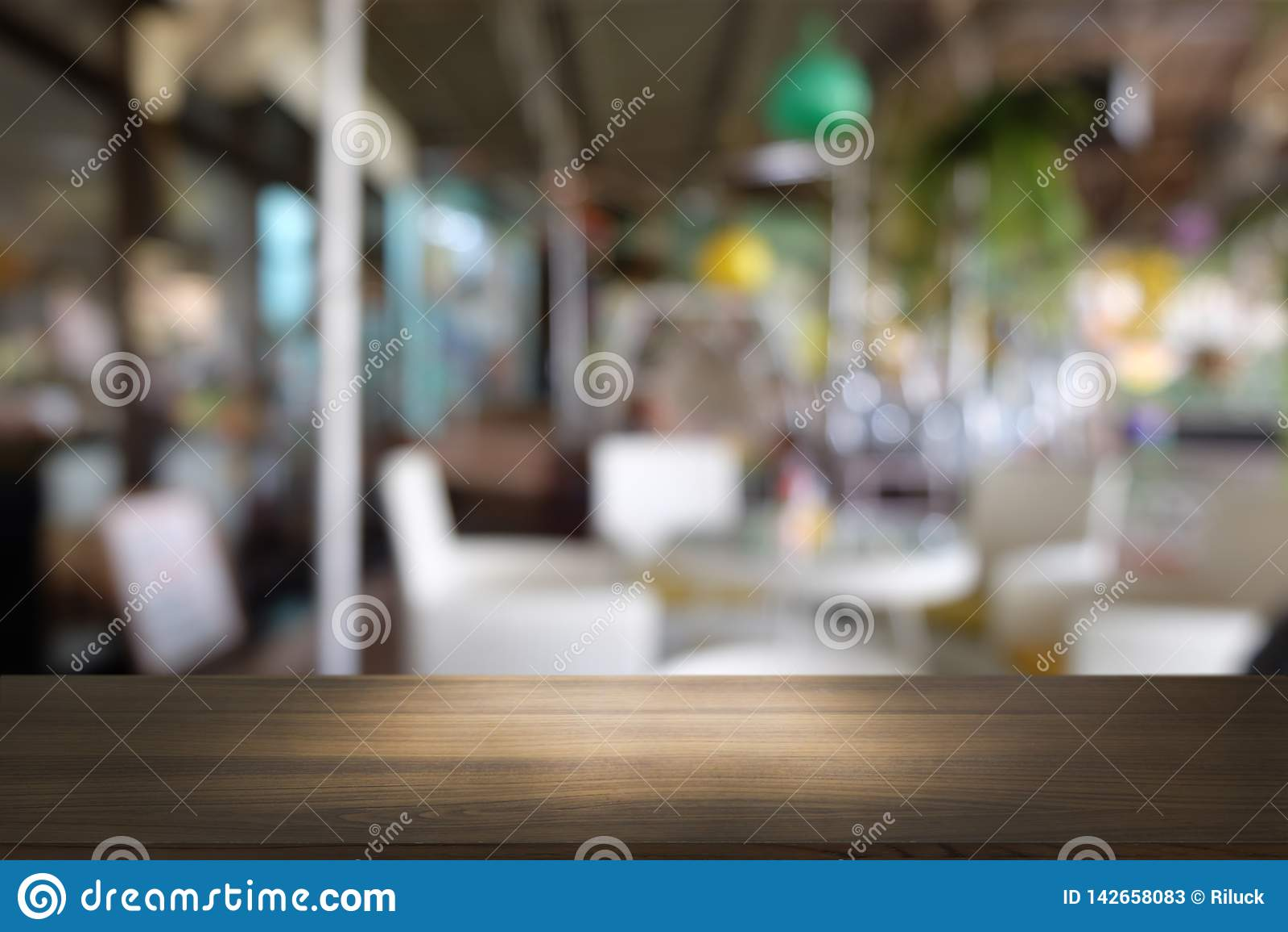在摘要前面的空的黑暗的木桌弄脏了餐馆bokeh背景