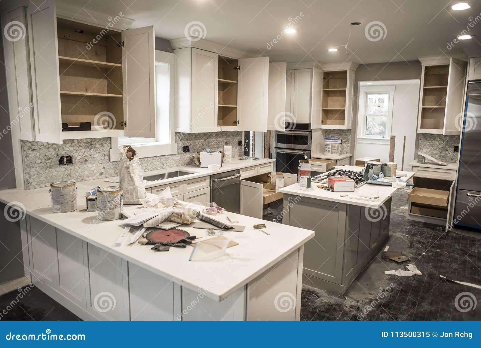 在改造的杂乱家庭厨房与橱门期间打开凌乱与油漆罐头、工具和肮脏的旧布,罐装云幂灯