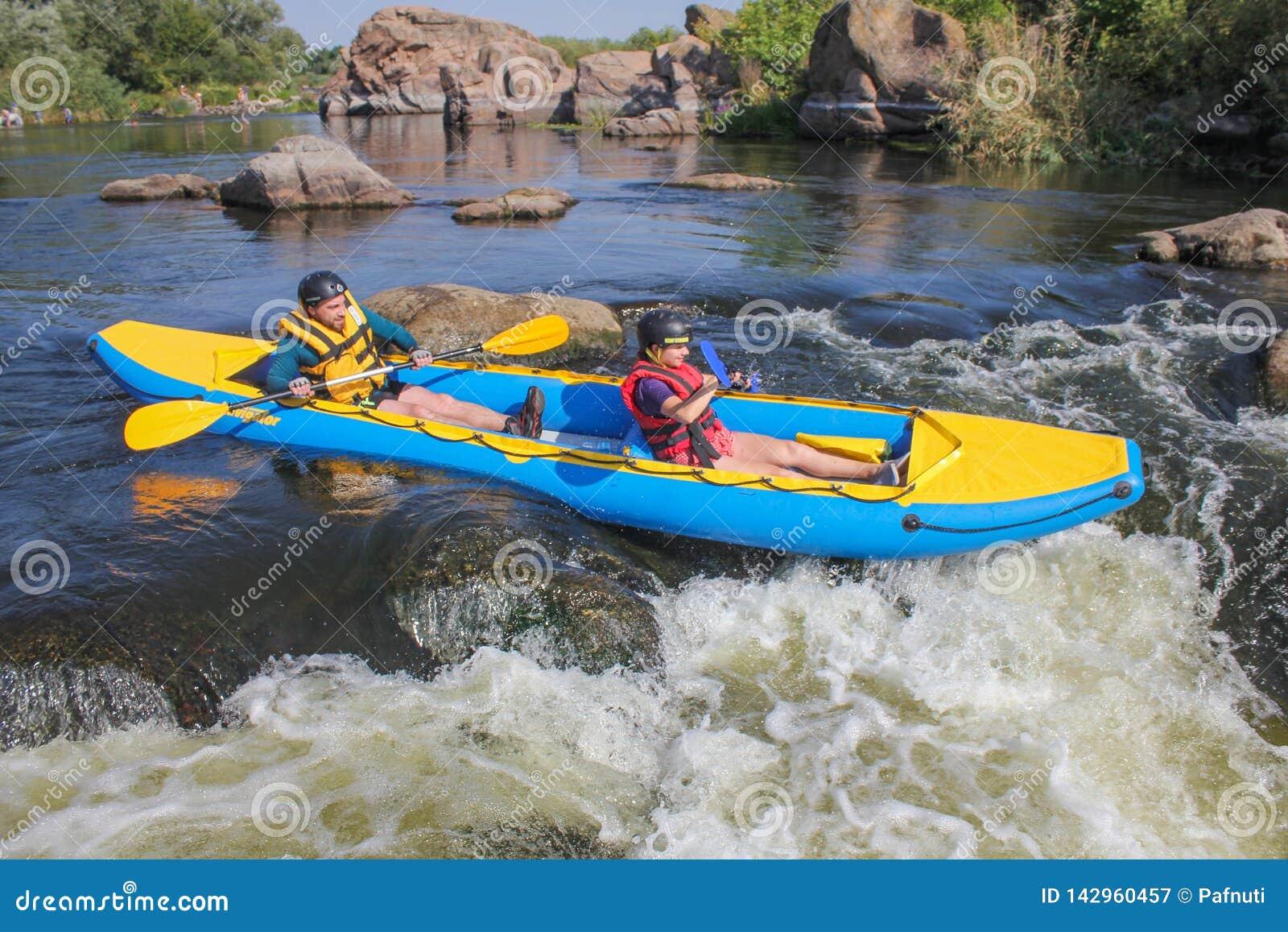 在救生背心的愉快的年轻夫妇微笑着,当航行皮船时