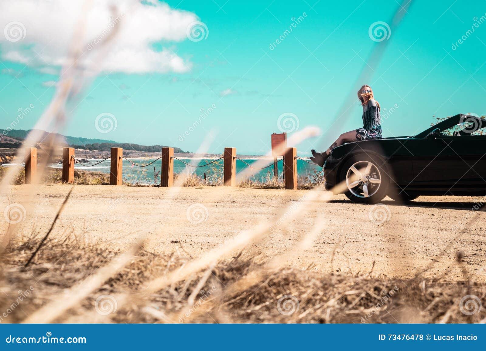在敞篷车顶部的女孩在半月湾,加利福尼亚