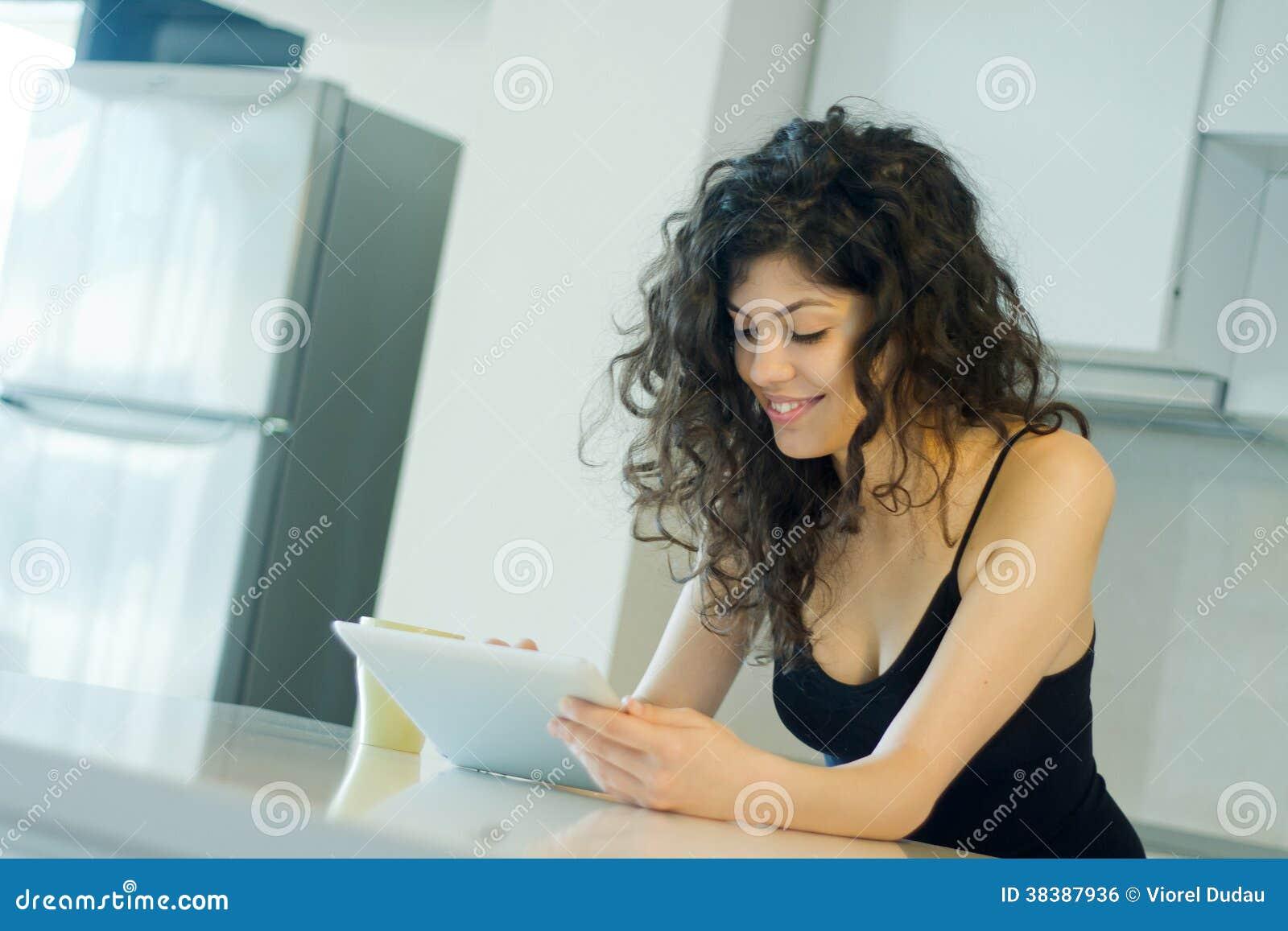 在数字式片剂的微笑的妇女读书
