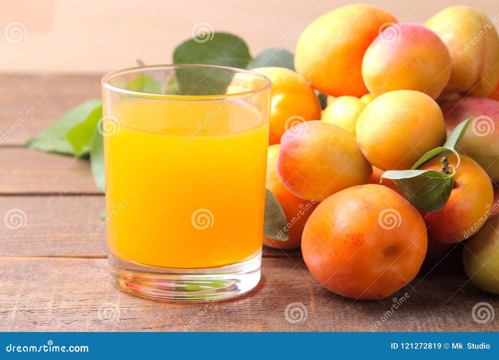 在新鲜的杏子旁边的杏子汁在棕色木背景