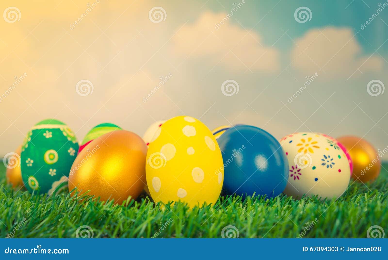 在新鲜的绿草的复活节彩蛋在蓝天(被过滤的图象