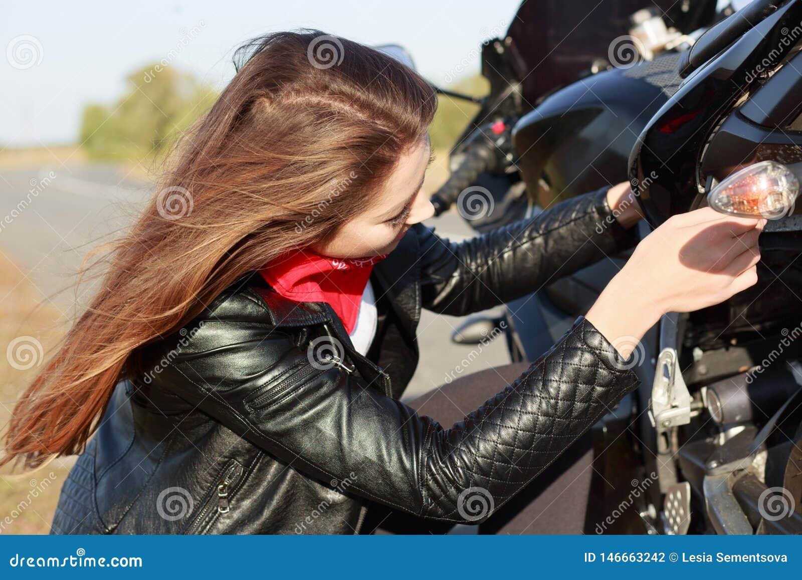 在旅行期间,女孩驾驶人接近的画象有长的黑发的在夹克,设法修理摩托车,修理有些零件,有