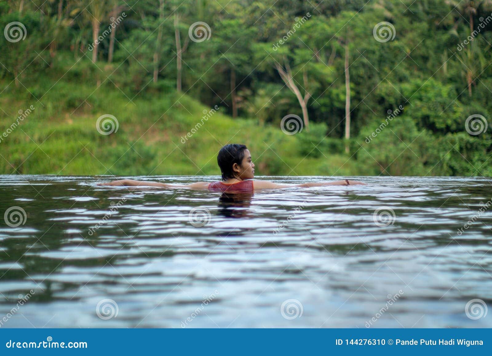 在无限水池的年轻亚洲女孩游泳有美丽的景色 她被拍从后面的照片
