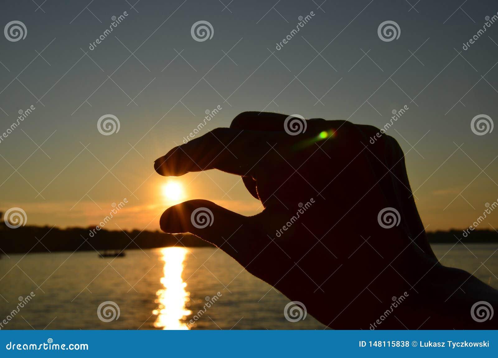 在日落期间,年轻女人递在手指之间的捉住的太阳