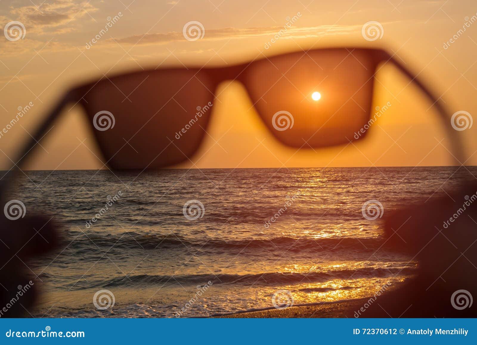 在日落海背景的太阳镜