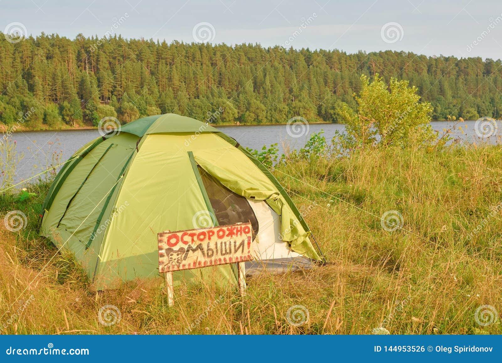 在日落的帐篷,在河岸的一个帐篷