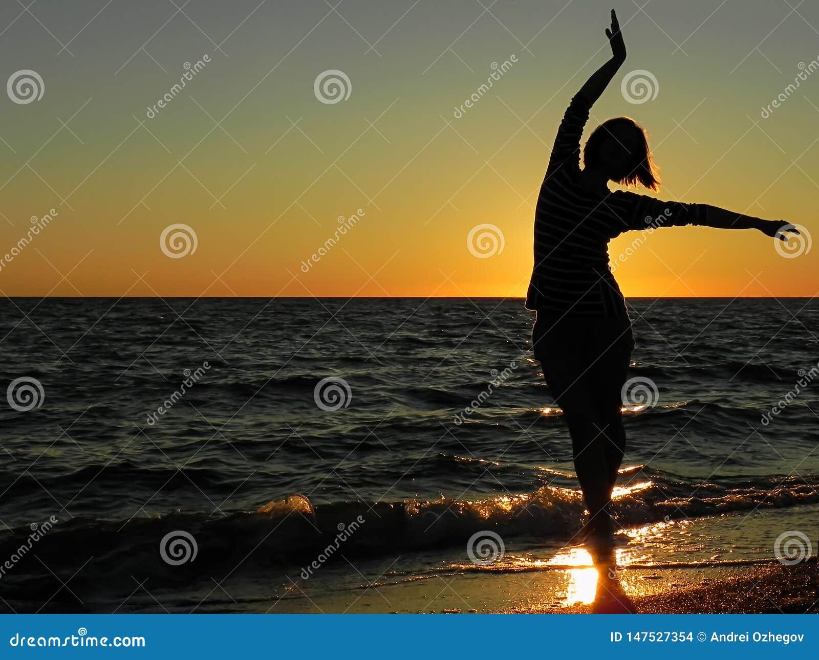 在日落的无忧无虑的妇女跳舞在海滩