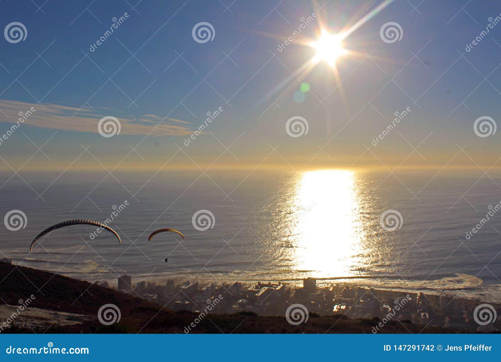 在日落的滑翔伞在开普敦