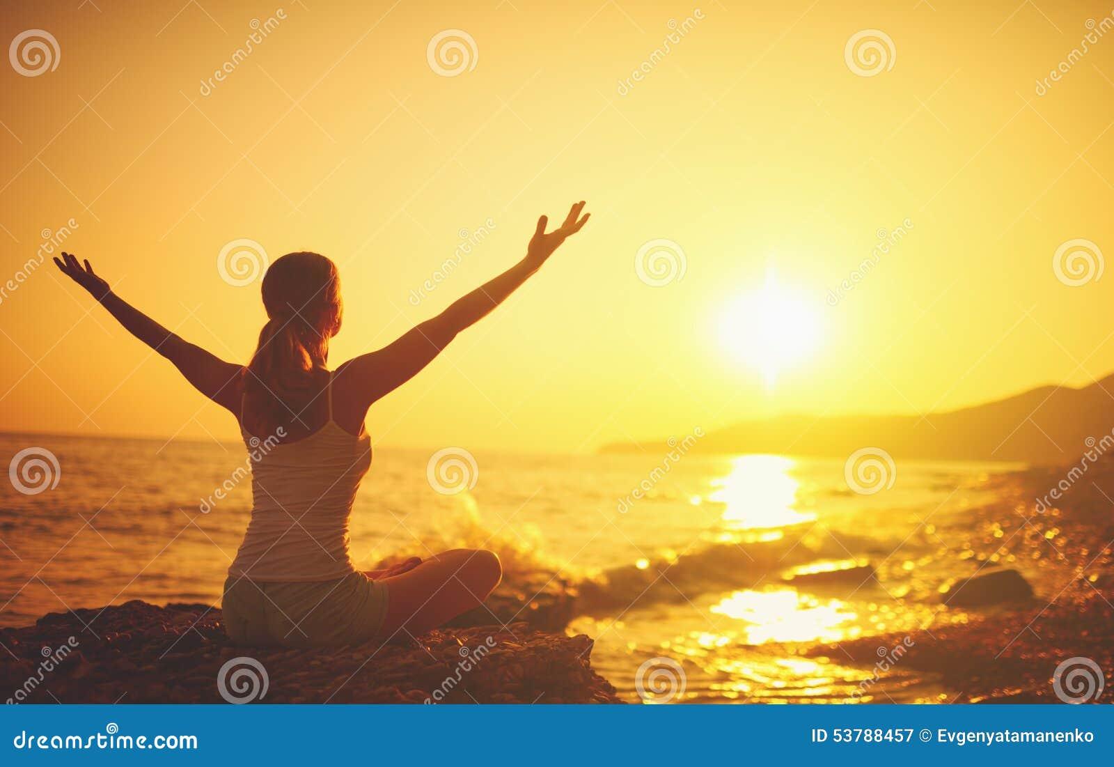 在日落的瑜伽在海滩 执行女子瑜伽