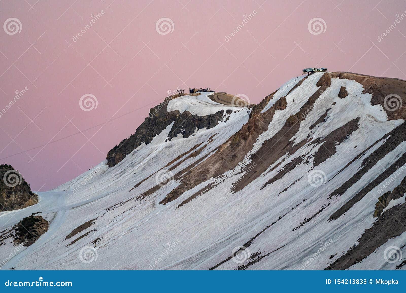 在日落的美丽的桃红色天空在马默斯Mountain滑雪地区的倾斜 在夏季仍然拍的照片,与雪在