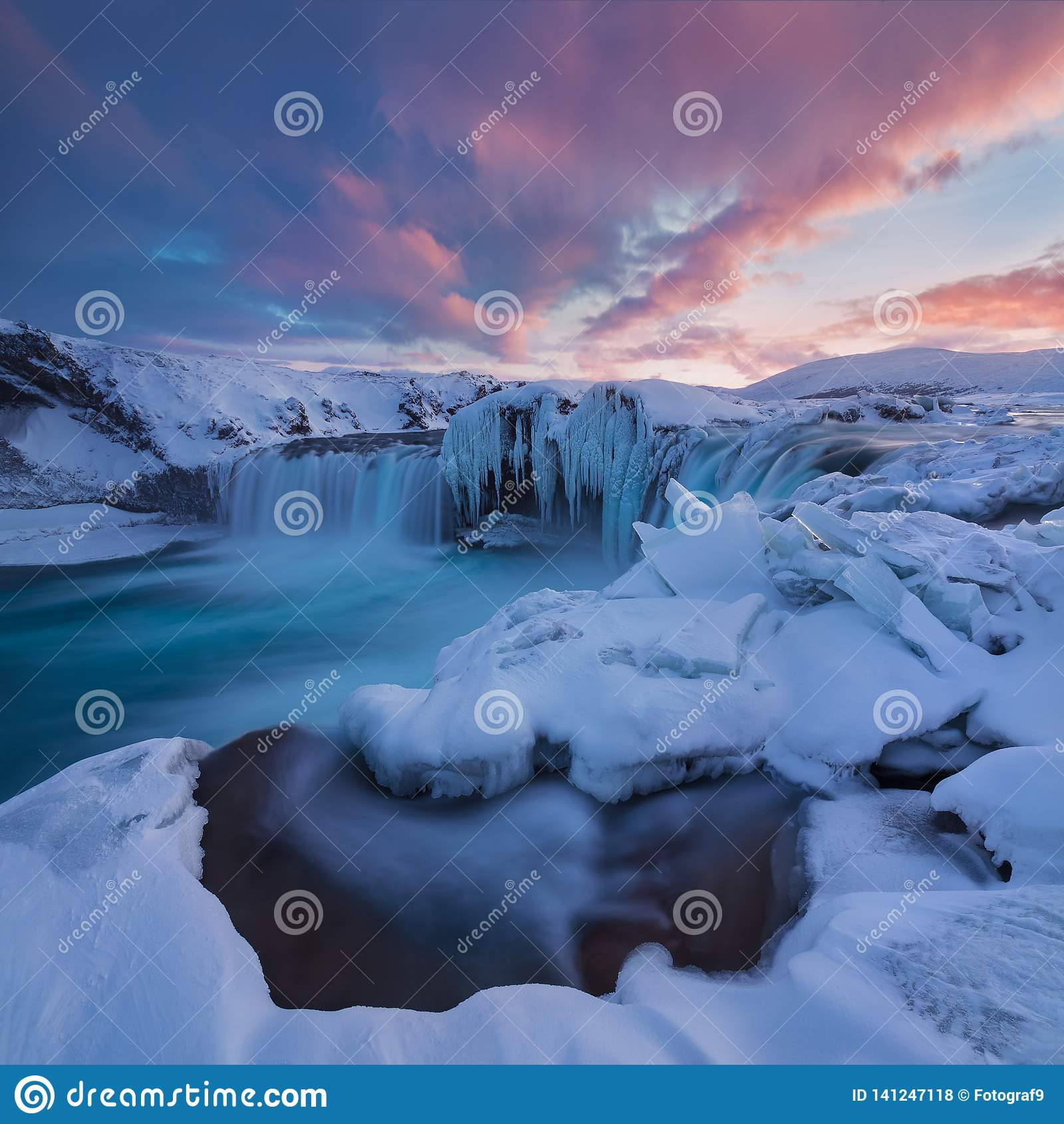 在日落视图的Godafoss瀑布在冰岛,北欧附近在与最强有力的瀑布的雪和冰一的冬天