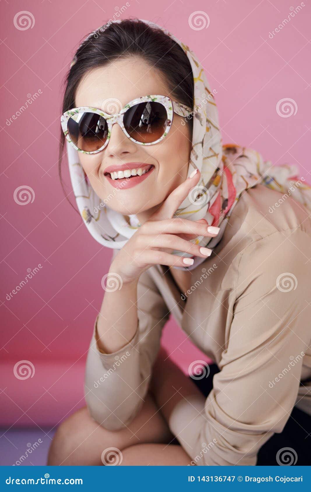 在时兴的镜片和精美丝绸围巾的快乐的美女耳环,在桃红色背景