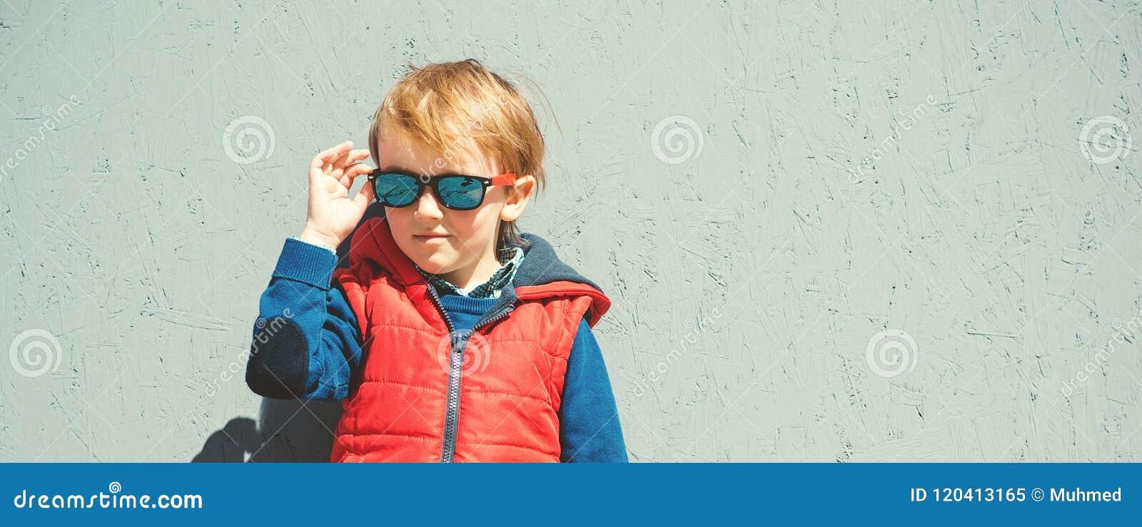 在时髦太阳镜的时髦的孩子 塑造孩子 逗人喜爱的一点blon
