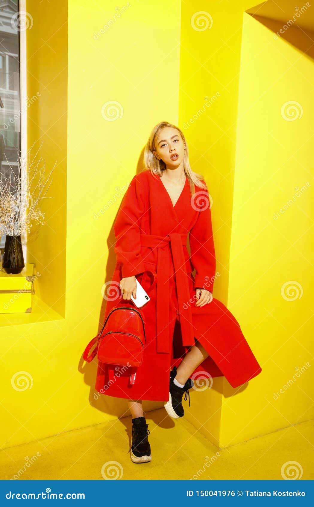 在时髦的红色外套打扮的美丽的少女博客作者在黄色墙壁背景摆在展示屋子