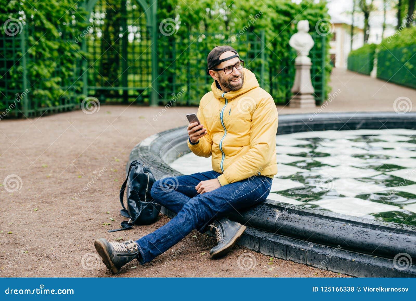 在时髦盖帽、滑雪衫、牛仔裤和eyewear的轻松的无忧无虑的有胡子的旅客男性有游览在坐在fo附近的森林储备