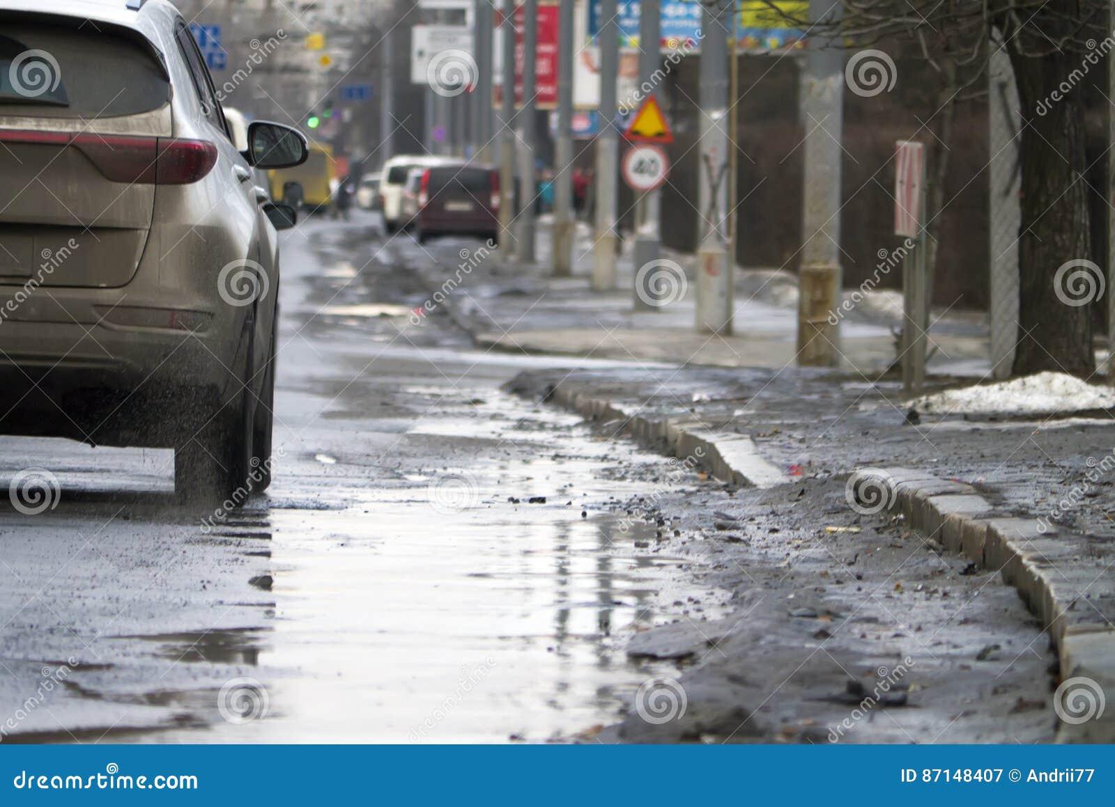 在春天解冻期间的城市交通 有水坑的路